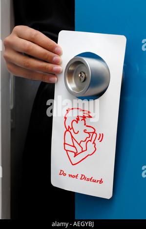 Woman hand putting door hanger Do not Disturb sign on a hotel doorknob - Stock Photo