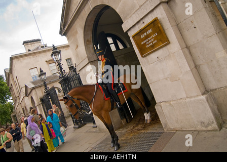 Angular horizontal wide angle of a female member of the Household Cavalry on duty mounted outside Horse Guards Parade - Stock Photo