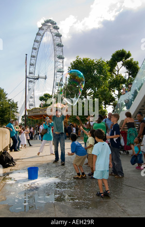 Vertical view of a street performer creating huge bubbles entertaining a crowd of children on the Southbank in London. - Stock Photo