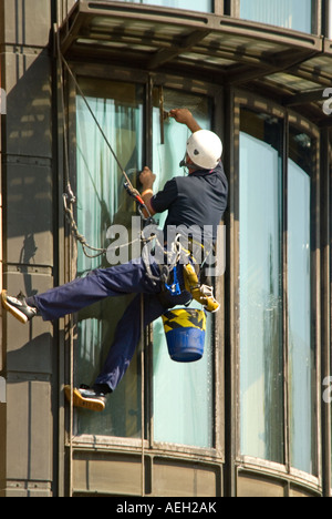 Vertical close up of a window-cleaner dangling precariously to clean windows - Stock Photo