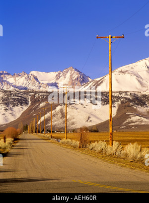 Road with power lines and Eastern Sierra Mountains California - Stock Photo