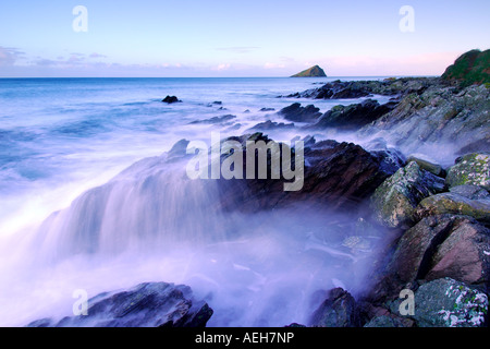 Beautiful dawn light at Wembury Beach South West Devon with the sea swirling around the exposed rocks - Stock Photo