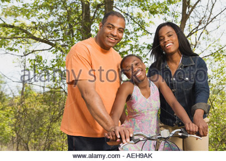 African girl on bicycle with parents in park - Stock Photo