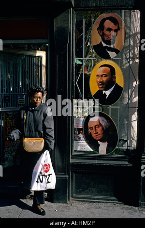 Shopper leaving a bookstore on Broadway displaying portraits of two U S Presidents and of Martin Luther King - Stock Photo