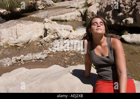 Young woman facing the sun seated on a rock with her eyes closed in the middle of a river - Stock Photo