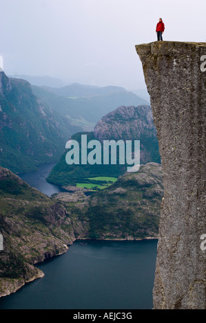 Hiker standing on Preikestolen cliff above Lysefjord, Rogaland, Norway, Scandinavia, Europe - Stock Photo