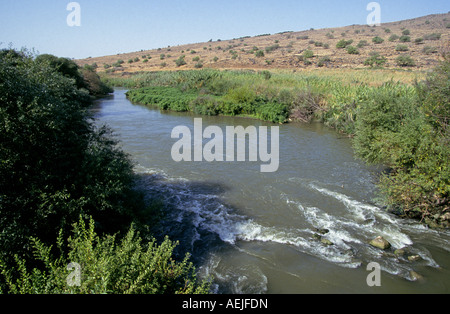 A view of the Jordan River as it flows through the desert just beneath the Golan Heights in the West Bank of Israel - Stock Photo