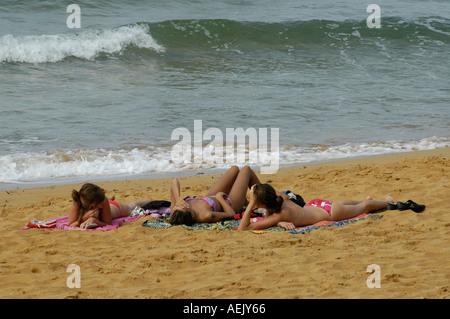 Women sunbathing in Golden Bay one of the few sand beaches on the north west coast of Pierce Newell near Għajn Tuffiena - Stock Photo