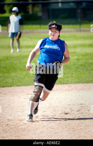 Overweight female with injured knee wearing brace runs on field - Stock Photo
