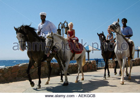 Young tourists horseback riding along promenade of Masbat Bay in Dahab  town on the southeast coast of the Sinai - Stock Photo