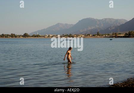 A tourist walking in the waters of Nuweiba Tarabin beach in Nuweiba also spelled: Nueiba a coastal town in the eastern - Stock Photo