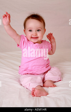 Cute newborn baby sitting upright at seven months laughing holding hands above head showing excitement joyful facial - Stock Photo