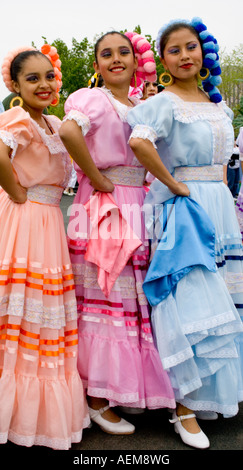 Three Chicana woman dancing in the parade. Cinco de Mayo Fiesta. 'St Paul' Minnesota USA - Stock Photo