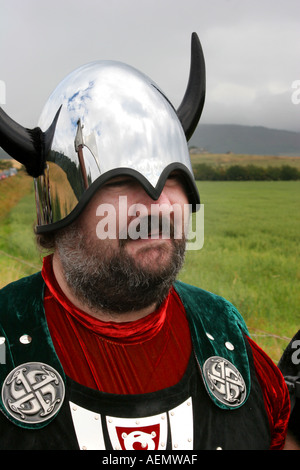 Viking Norse men Shetland marchers Tarland Highland Games stainless steel helmets axes roar entertainers man outside - Stock Photo
