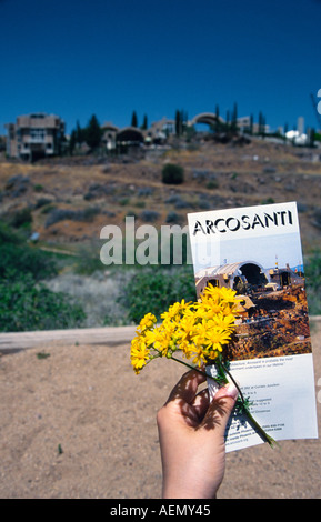 hand hold a flyer and yellow flower at arcosanti experimental town in the desert mayer arizona usa - Stock Photo