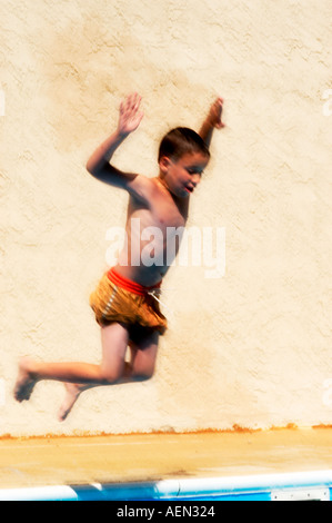 portrait of small boy playing in pool , young boy playing in water, jumping into water - Stock Photo