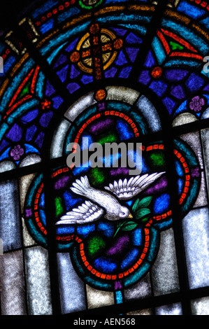 Stained glass window depicting cross and dove holding olive branch Colorado Springs, Colorado, USA. - Stock Photo