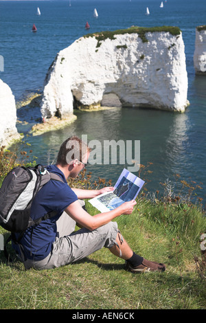 Student studying a map on a hike along the cliffs near to Old Harry Rocks on the Studland Peninsula, Dorset, England. - Stock Photo
