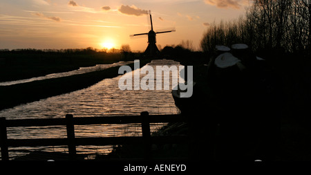 Windmill silhouette on the horizon, against fading sunlight with some clouds, at the end of a waterway, Vlist, The - Stock Photo
