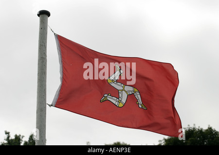 Red manx flag flying in the wind from flagpole Isle of Man - Stock Photo