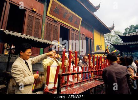 Hangzhou Zhejiang China Lingyin Temple Temple of the Soul s Retreat with pilgrims lighting joss sticks of incense - Stock Photo