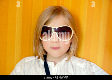 Cool girl with sunglasses standing in front of a yellow and striped wall-paper - Stock Photo