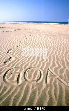 India word Goa written in rippled sand with line of footsteps - Stock Photo