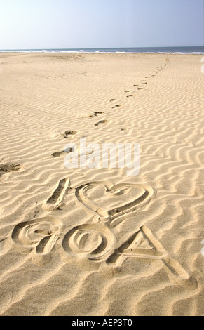 India Goa I love Goa written in rippled sand with line of footsteps - Stock Photo