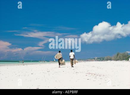 Two black African basket sellers strolling along Diani Beach Kenya coast East Africa - Stock Photo