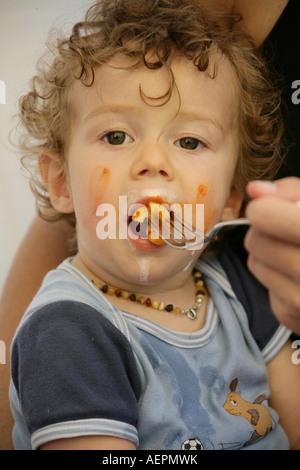 Kleinkind 18 Monate alt JONI mit Bernsteinkette um den Hals beim Essen mit verschmiertem Gesicht Model Released - Stock Photo