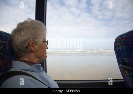 Lady tourist sat looking out through coach window on Ninety Mile Beach with rough sea Aupori Peninsula New Zealand - Stock Photo