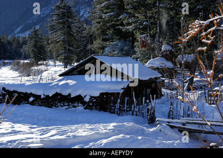 A beautiful landscape of a hut covered under snow during winter season at village Rakcham, Sangla valley Himachal - Stock Photo