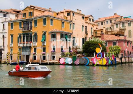 Small private boat passes a Biennale art exhibit on the Grand Canal near the Academia Bridge San Marco area Venice - Stock Photo