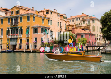 Water taxi passes Biennale art exhibit on the Grand Canal near the Academia Bridge San Marco area Venice Italy - Stock Photo