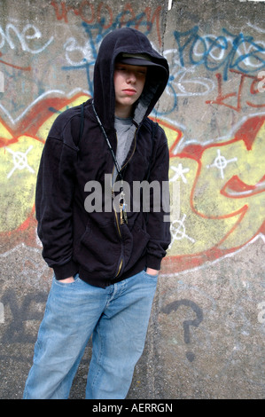 Young boy hanging around the streets dressed in hoodie looking threatening and bored - Stock Photo