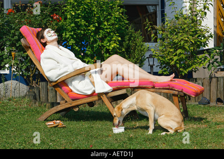 woman on deck chair - young half breed dog drinking - Stock Photo