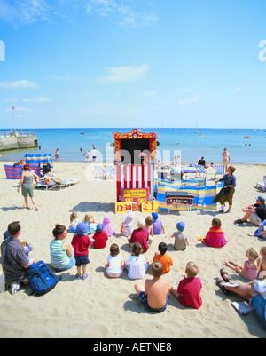 GB DORSET SWANAGE BEACH CHILDREN WATCHING PUNCH AND JUDY SHOW - Stock Photo
