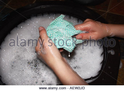 the hands of a 10 year old boy washing up in soapy water - Stock Photo