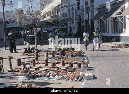 Three young African women walk past wooden carvings on the pavement in Windhoek Namibia south west Africa - Stock Photo