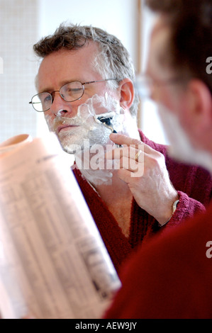 British business man ready the financial times whilst shaving in the morning getting ready for work in the city - Stock Photo