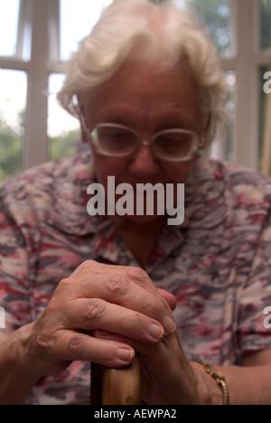 81 year old elderly woman leaning on her walking stick, London, UK. - Stock Photo