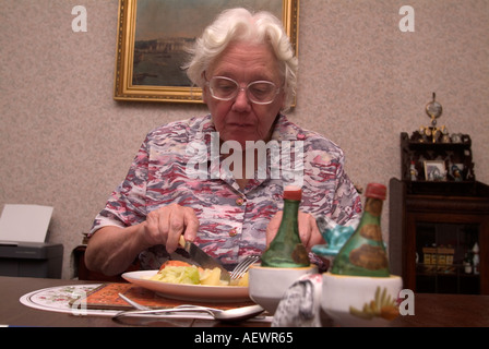 81 year old elderly woman eating her self prepared lunch London UK - Stock Photo