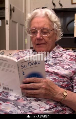 81 year old elderly woman reading Sudoku book London UK - Stock Photo