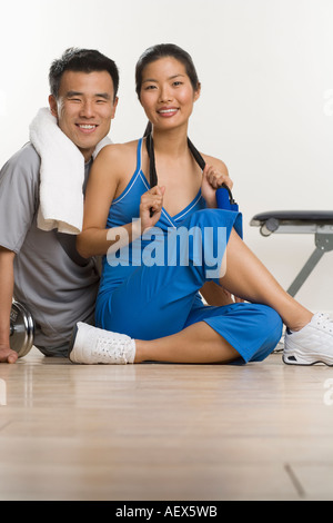 Portrait of man and woman working out - Stock Photo