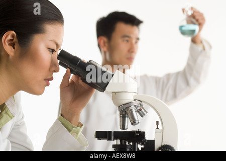 Scientists with beaker and microscope - Stock Photo