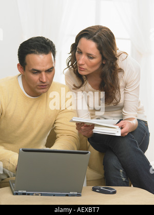 Couple working together at computer - Stock Photo