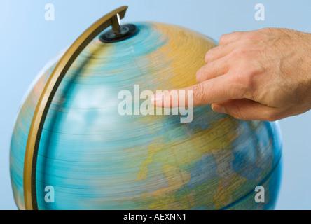Hand spinning globe - Stock Photo