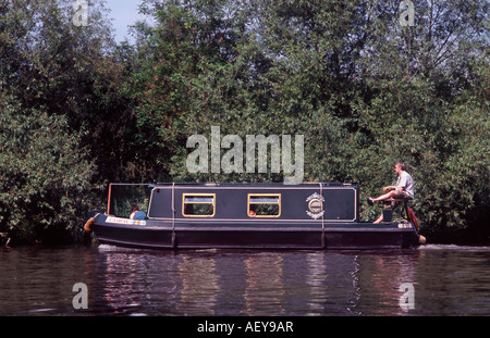 Man with leg up in the sun steering a short Sea Otter narrowboat on the River Thames above Boveney Lock, Windsor, - Stock Photo