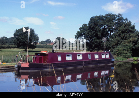 Liveaboard narrowboat with wind generator and TV mast on a residential mooring, Shropshire Union Canal, near Brewood, - Stock Photo