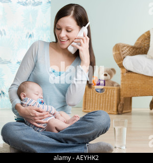 Mother on telephone with sleeping baby in her lap - Stock Photo
